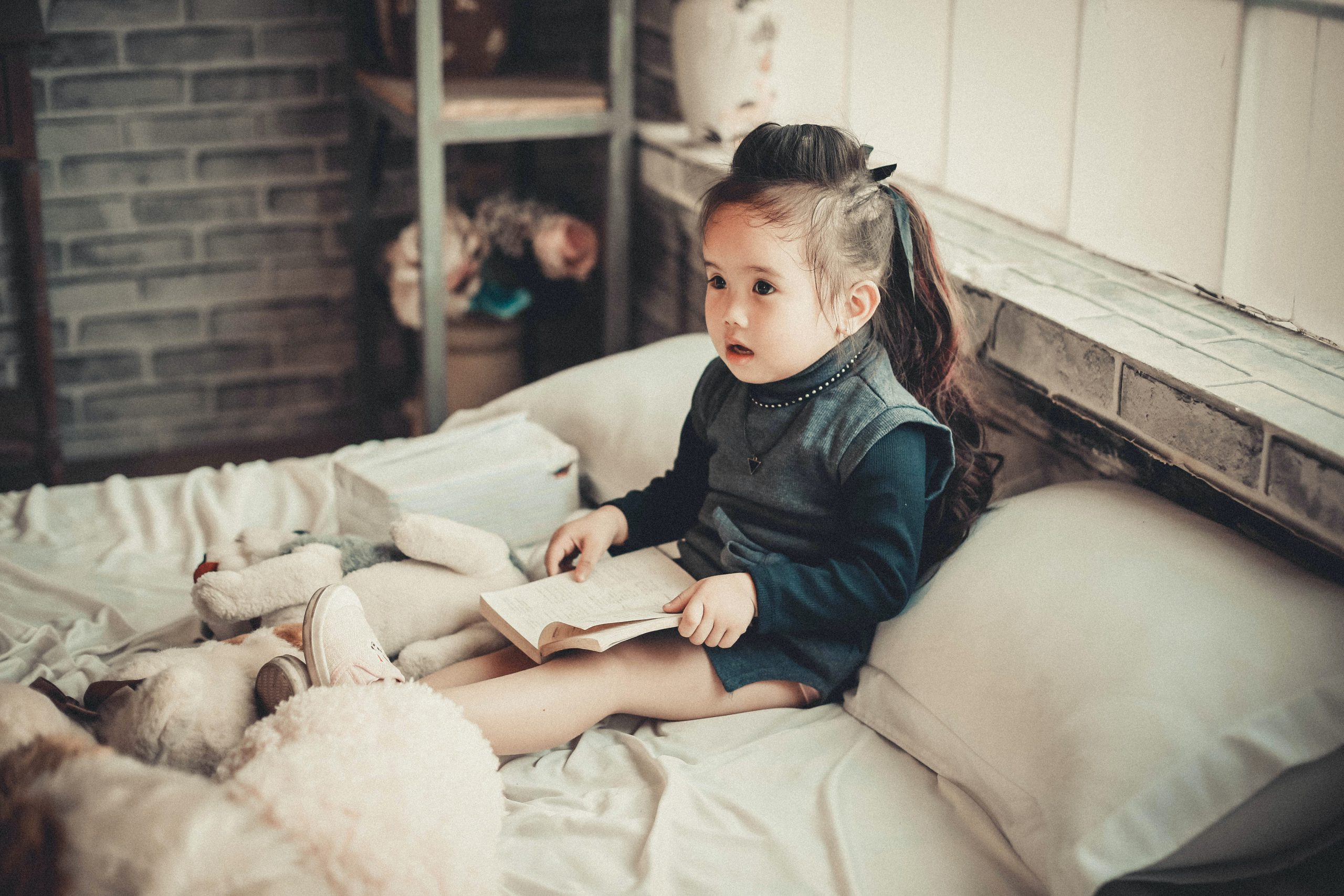 Girl sitting in bed reading a book