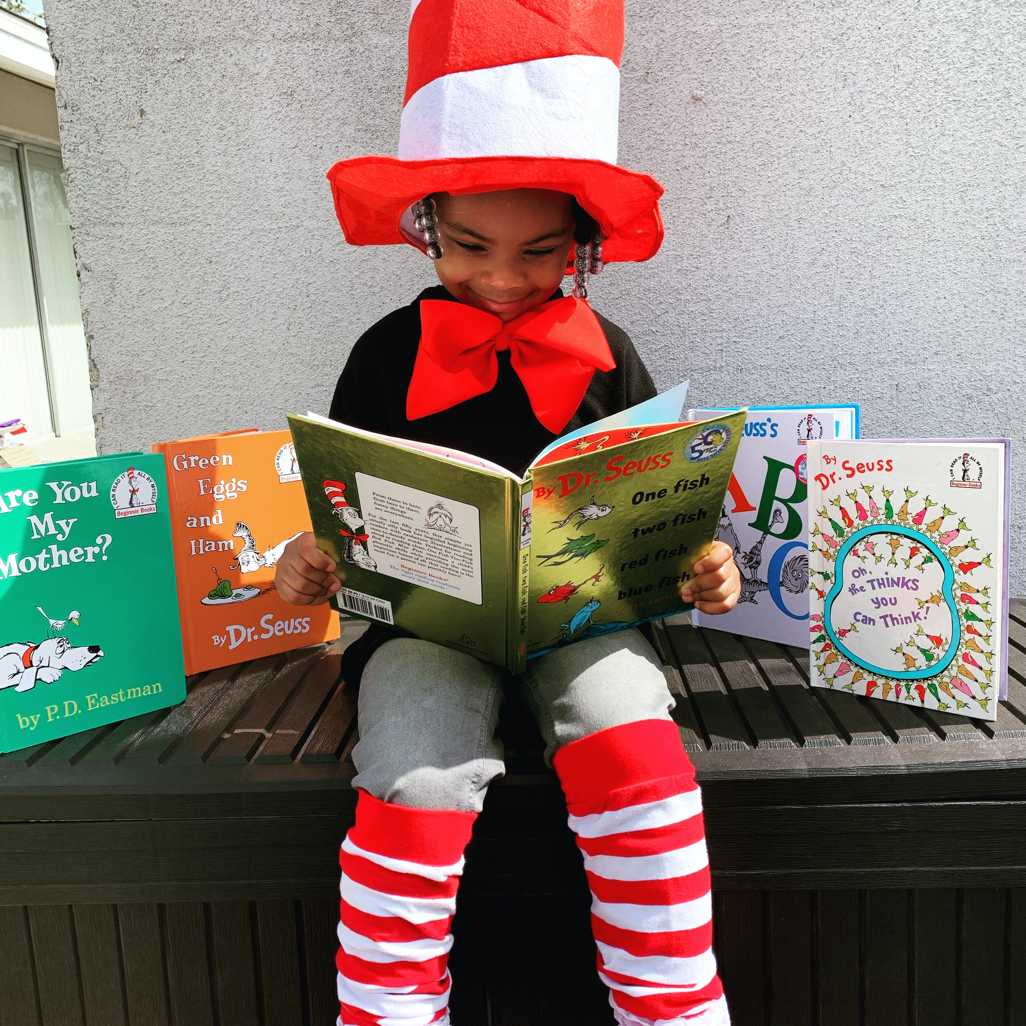 Child in red hat reading a book