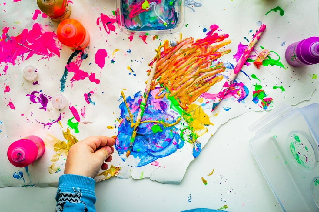 A white table splattered with colorful paints