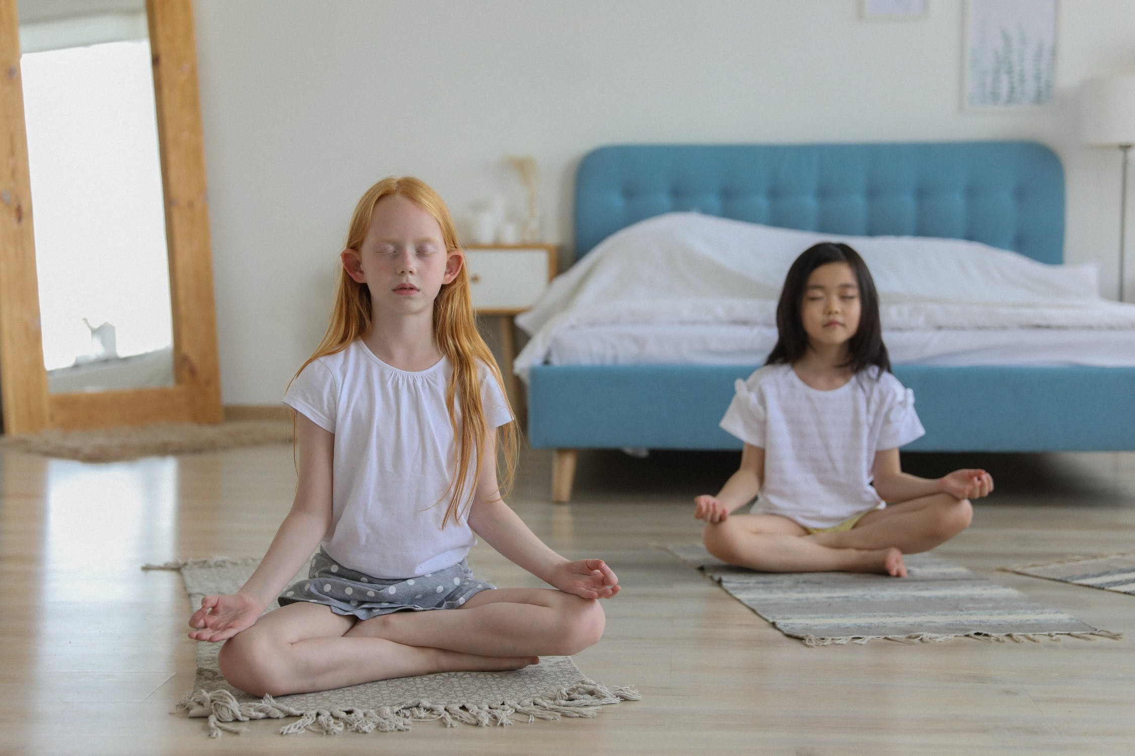 two children meditate in a bedroom