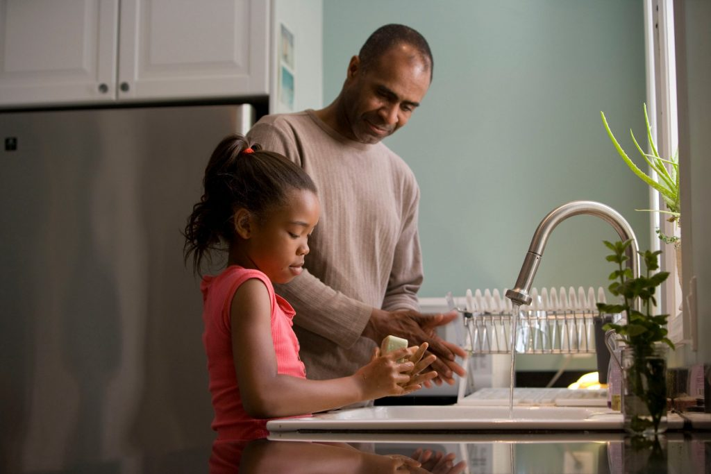 A man with a girl washing her hands at the kitchen sink.
