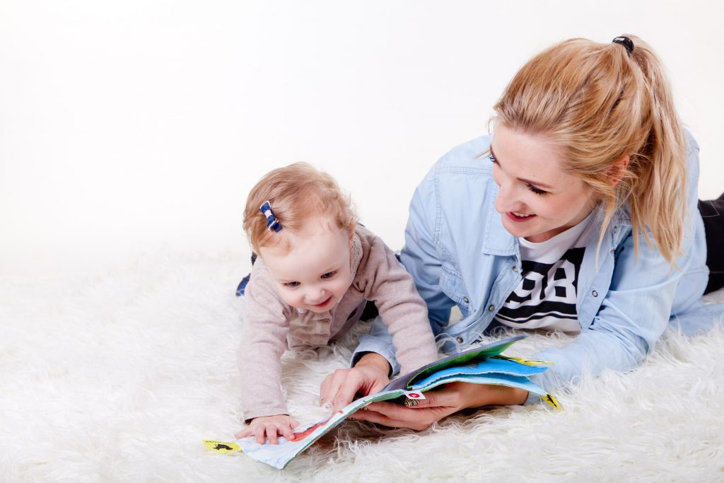 A mother and baby girl reading a book.