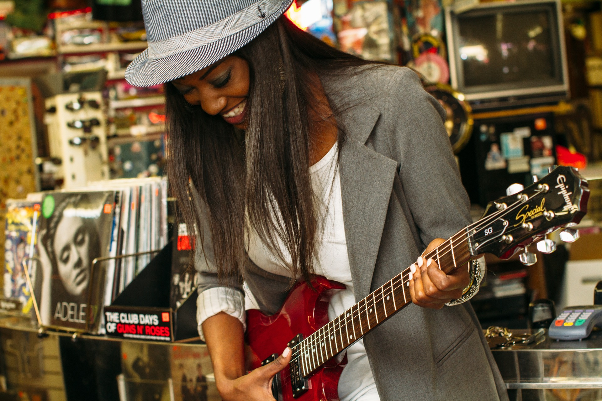 A woman with a hat playing an electric guitar.