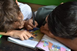 young boys looking at book together