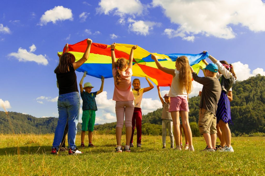 kids standing in a circle outside holding up a parachute