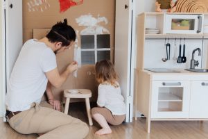 father and girl painting cardboard house