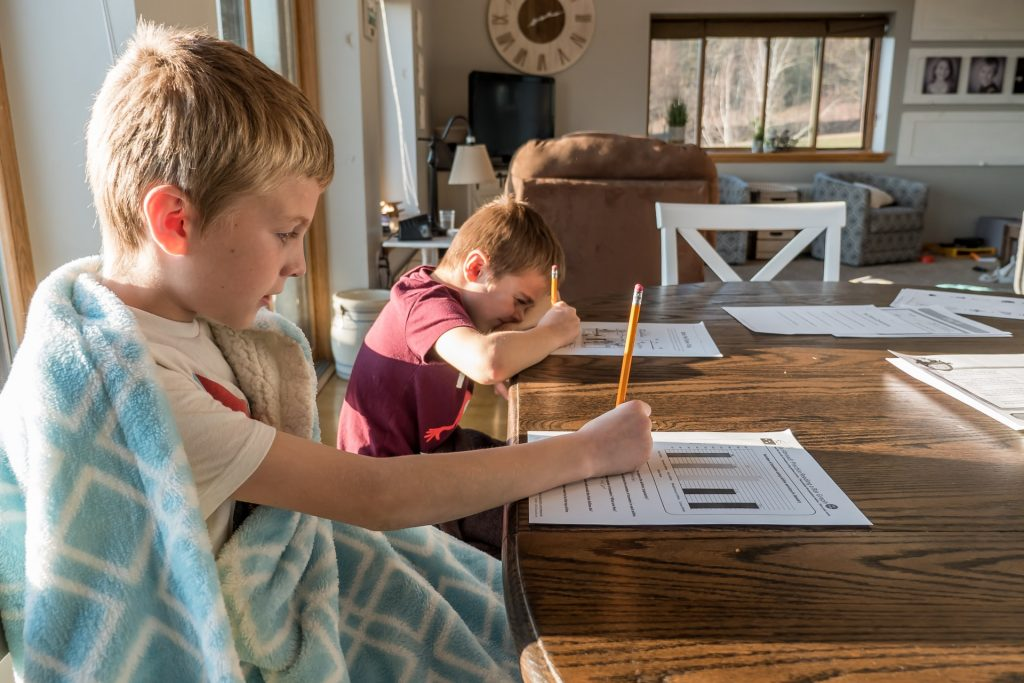 two young boys doing homework at a kitchen table