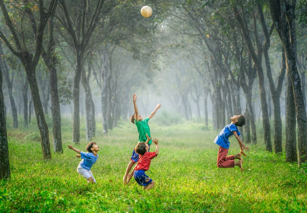 four young boys playing ball in green grass