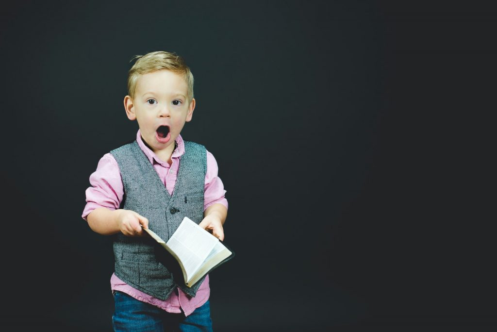A young boy surprised at a book
