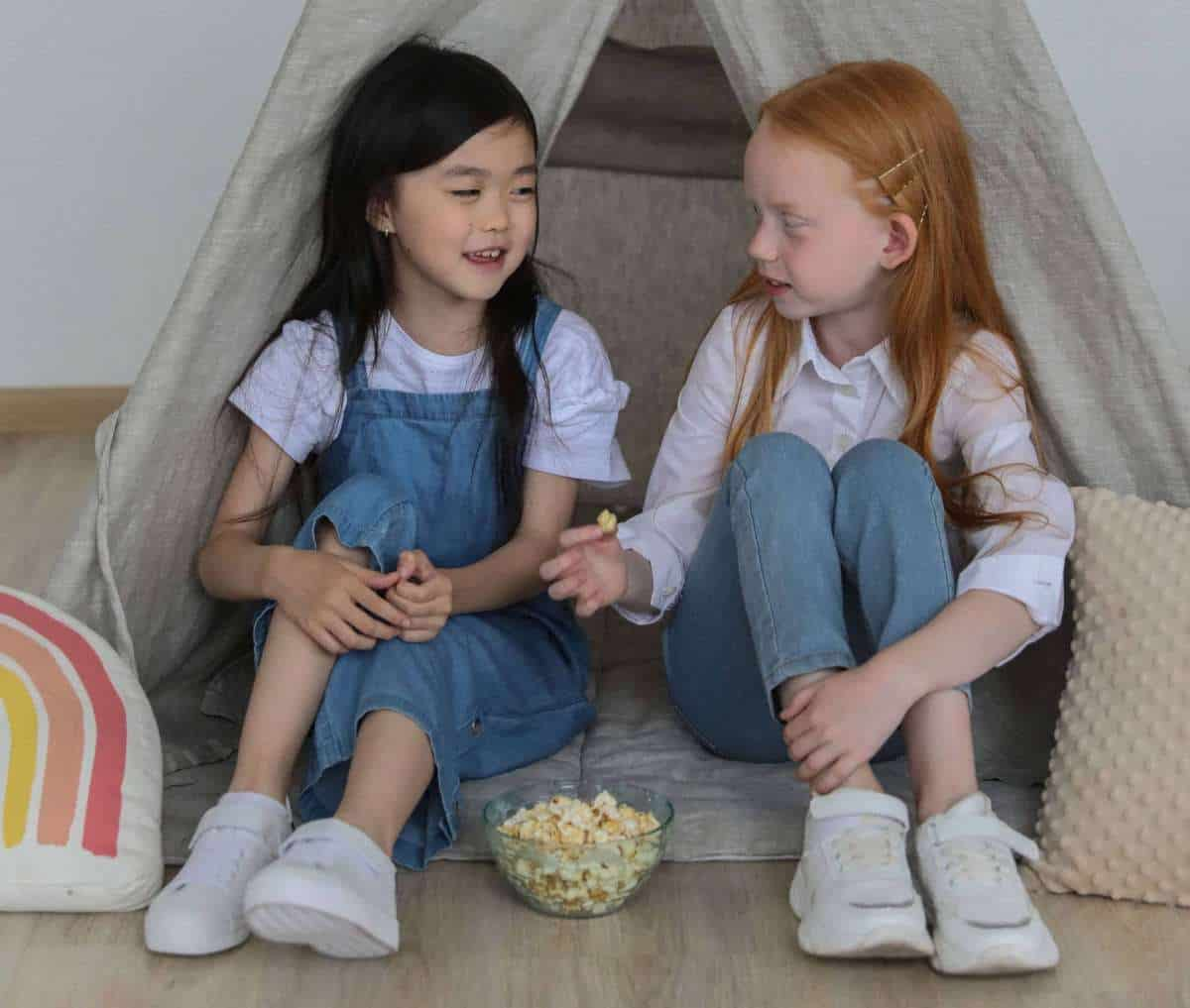children eating popcorn by a tent