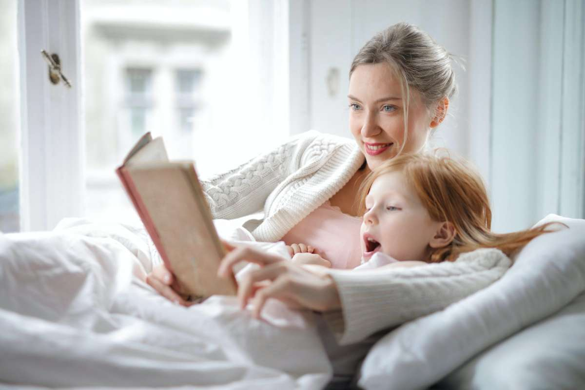 Woman on a couch reading with her child