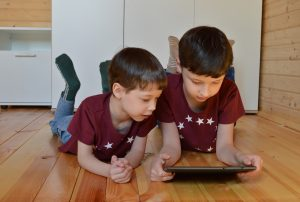 two boys watching a tablet